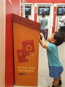Toddler in blue trying to read the words on a red ang bao recycling bin located in a DBS branch