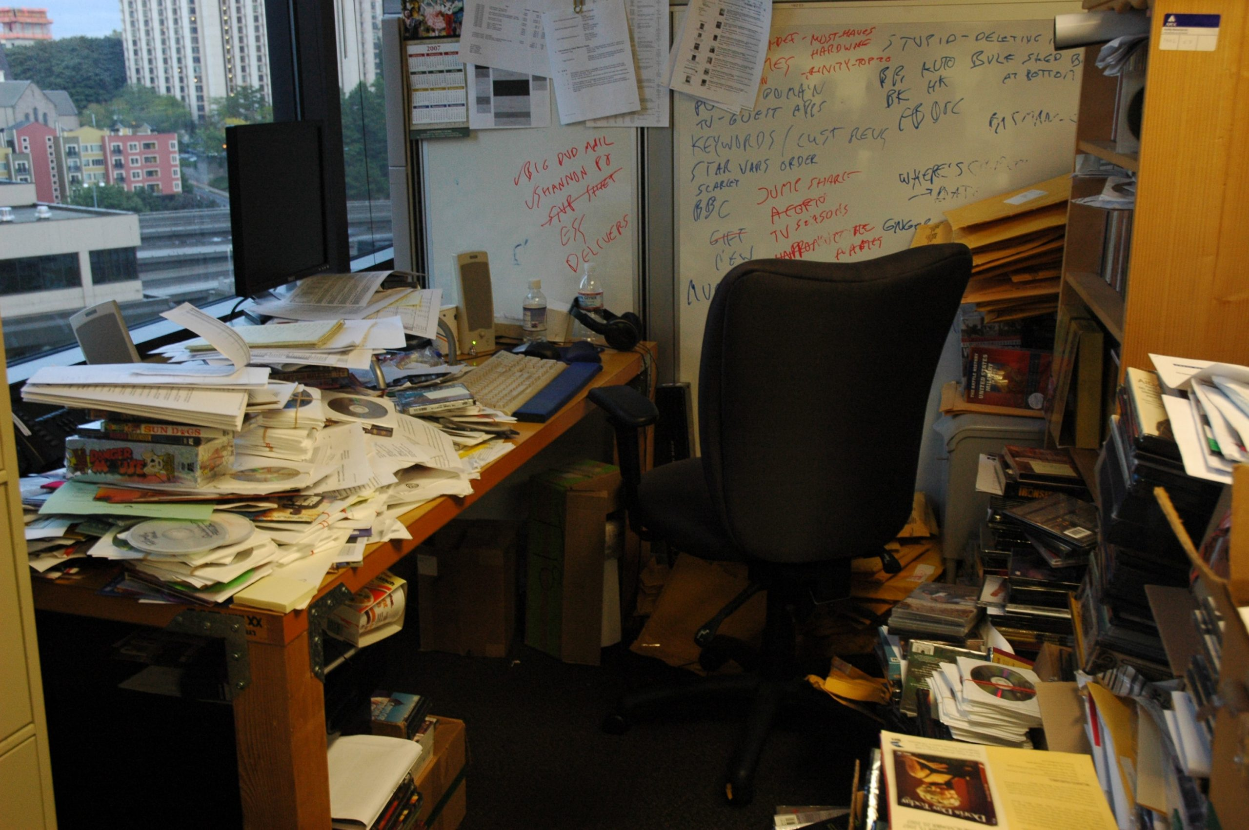 A cluttered home office with table and floor filled with piles of paper