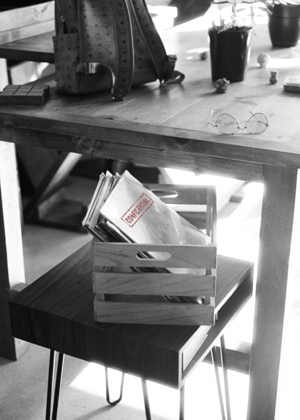 confidential document left in a wooden crate sitting on a chair next to a wooden table. grey scale picture.